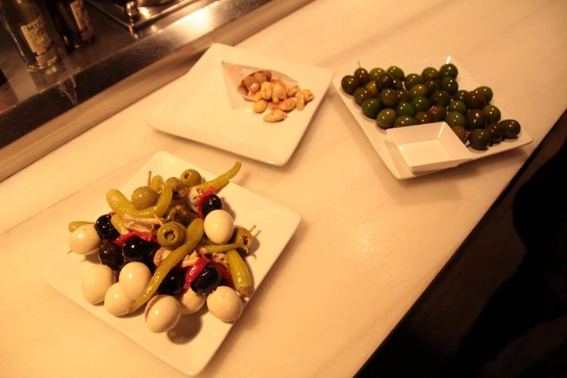 Quail egg, anchovy, olive & pickled pepper skewer, Campo Real olives and Marcona almonds. Delicious.